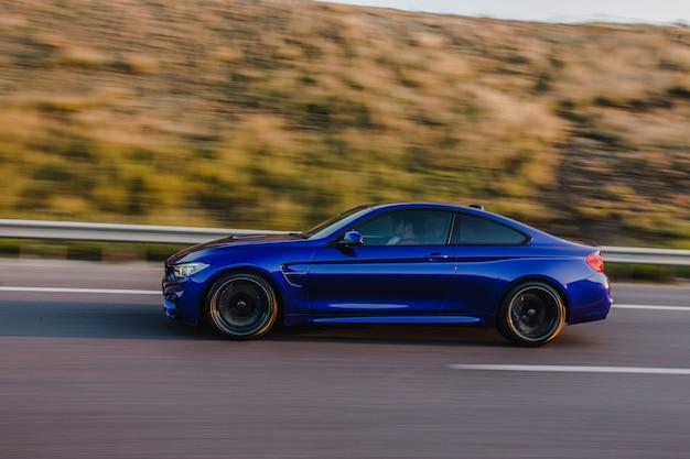 Sedan de esporte azul marinho na estrada. vista lateral.