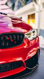 Sedan modelo vermelho no estacionamento marco, luz frontal e vista do pára-choques