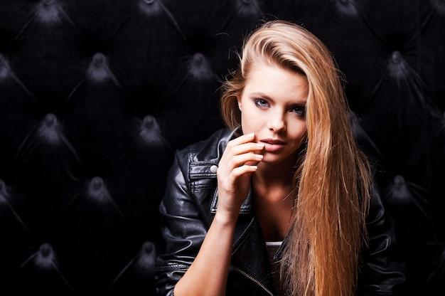 Seduzindo você. mulher jovem e bonita com maquiagem e posando contra um fundo preto