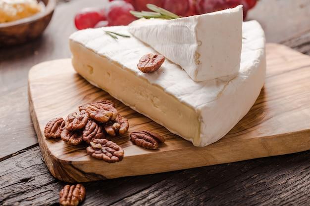 Segmento de queijo brie ou vaca macia - camembert francês na placa de madeira com uvas, favo de mel e nozes pecã.