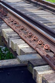 Segmento ferroviário curto, com destaque para trilhos, parafusos e travessas