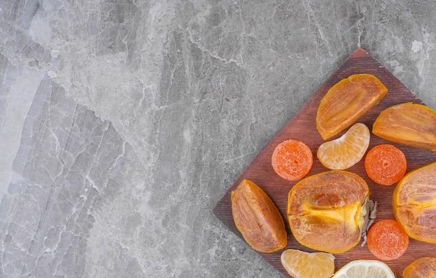 Segmentos de caqui e tangerina fatiados em uma tábua de madeira.