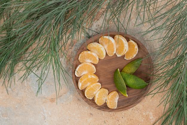 Segmentos de tangerina fresca na placa de madeira.