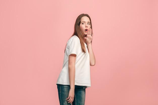 Segredo, conceito de fofoca. jovem adolescente sussurrando um segredo atrás da mão isolada em um rosa moderno