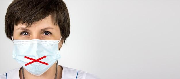 Segredo médico e não divulgação do conceito de diagnóstico. médica da mulher na máscara com os lábios colados, uniforme branco sobre fundo branco. conceito de sigilo médico.
