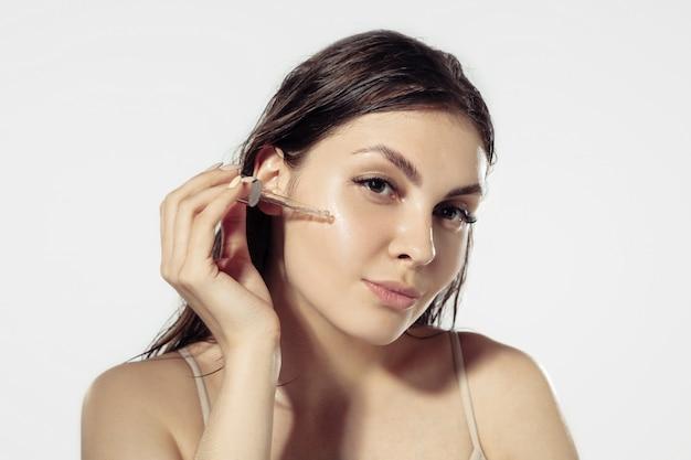 Segredos da juventude. mulher jovem e bonita parede branca. cosméticos e maquiagem, tratamento natural e ecológico, cuidados com a pele.