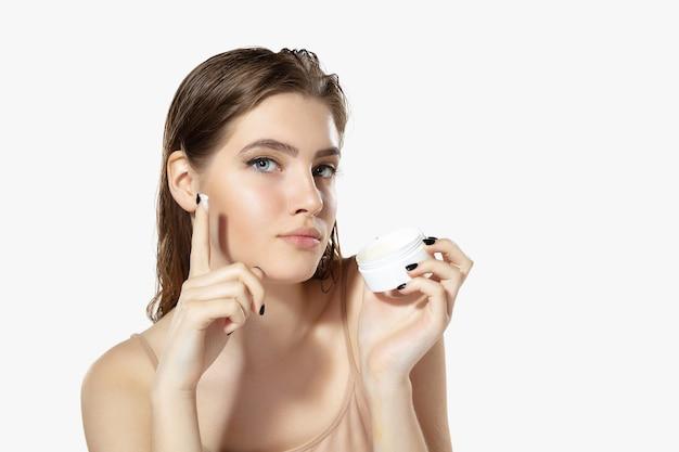 Segredos da juventude perto de uma bela jovem com hidratante sobre cosméticos de fundo branco e