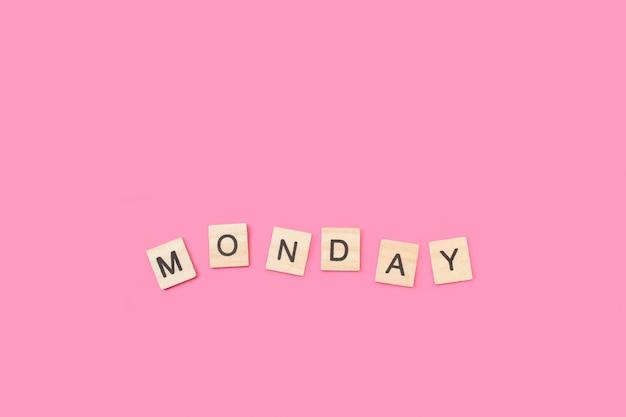 Segunda-feira, escreva com cubos de letras de madeira em um fundo rosa