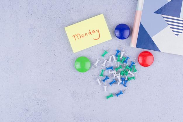 Segunda-feira escrevendo em um adesivo com um alfinete vermelho ao lado