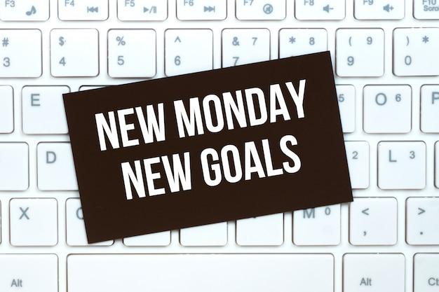 Segunda-feira novos objetivos, cartão de papel motivacional artesanal sobre o teclado do computador