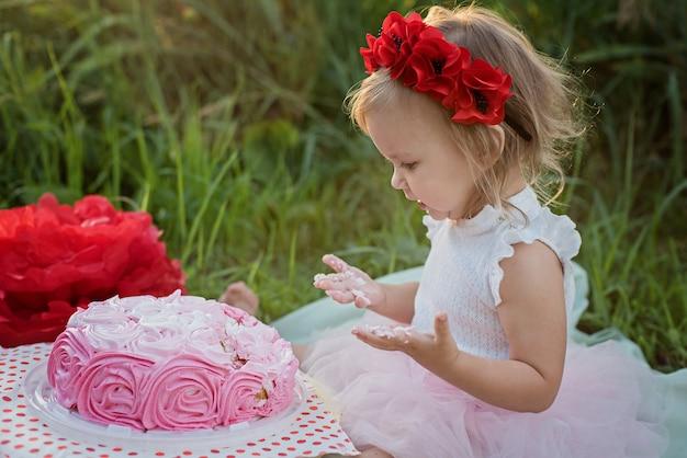 Segundo aniversário da menina. dois anos de menina idosa que senta-se perto das decorações da celebração e que come seu bolo de aniversário. bolo quebra.