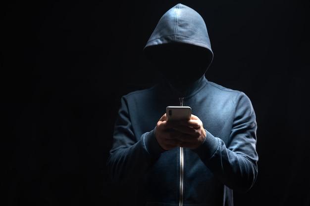 Segura o telefone em uma cena escura. conceito de hacker