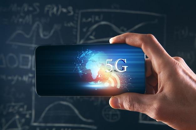 Segura um telefone com um planeta e 5g em um fundo de quadro-negro