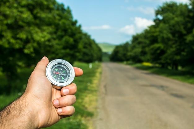 Segura uma bússola no fundo da estrada e nas árvores