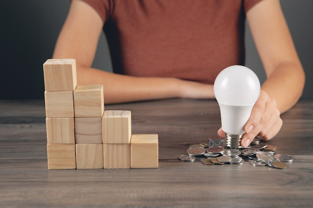 Segura uma lâmpada perto de uma moeda ao lado de uma escada de cubos