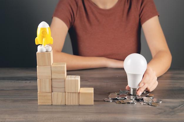 Segura uma lâmpada perto de uma moeda e um foguete fica em uma escada de cubos