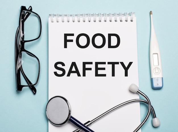 Segurança alimentar escrita em um bloco de notas branco ao lado de um estetoscópio, óculos de proteção e um termômetro eletrônico