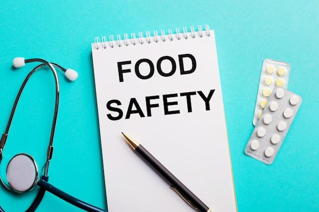Segurança alimentar escrita em um bloco de notas branco perto de um estetoscópio, canetas e comprimidos em uma parede azul clara. conceito médico