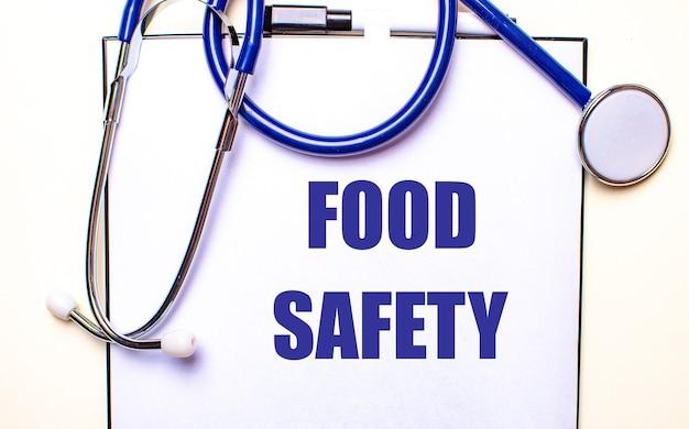 Segurança alimentar está escrita em uma folha branca perto do estetoscópio. conceito médico