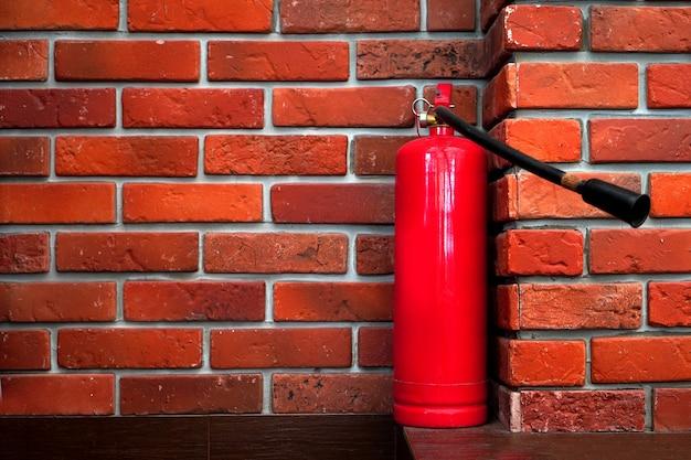 Segurança contra incêndio com extintor de incêndio na parede de tijolos vermelhos