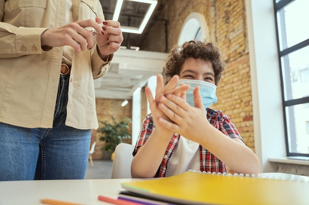 Segurança é importante garotinho brincalhão usando máscara protetora, limpando as mãos femininas