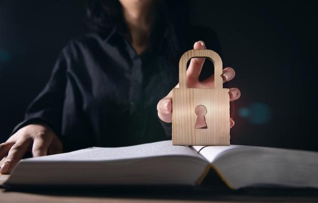 Segurança empresarial e conceito de proteção, mulher segurando cadeado e livro