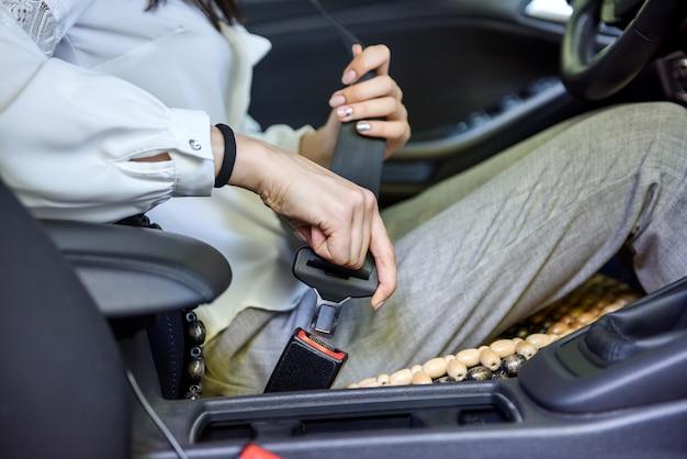 Segurança na estrada. mulher segurando o cinto de segurança do motorista sentada dentro do carro