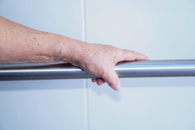 Segurança paciente asiática do punho do banheiro do toalete do uso da mulher sênior no hospital.