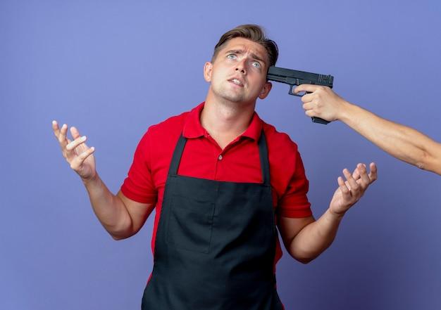 Segurando a arma na direção do templo de um jovem barbeiro loiro com medo de uniforme olha para cima com as mãos levantadas, isoladas no espaço violeta com espaço de cópia