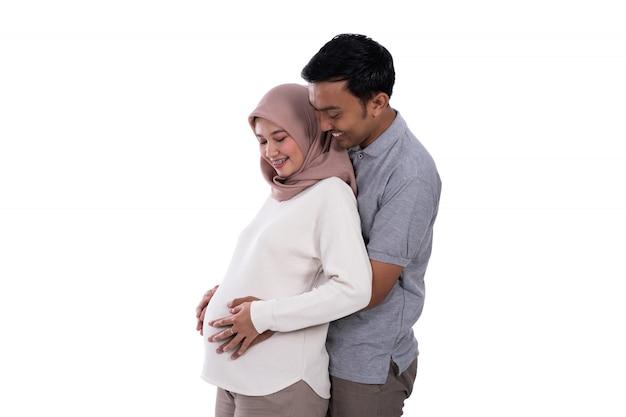 Segurando a barriga grávida de marido e mulher
