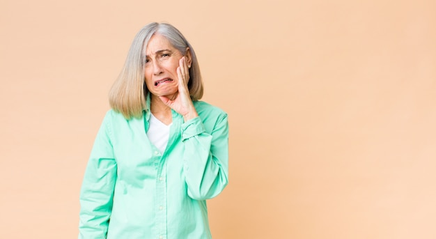 Segurando a bochecha e sofrendo dor de dente dolorosa, sentindo-se doente, infeliz e infeliz, procurando um dentista