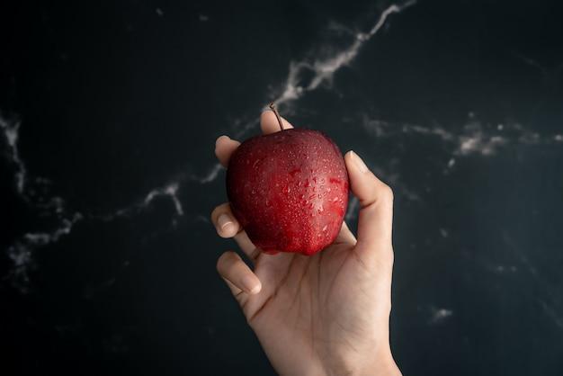 Segurando a maçã vermelha suculenta fresca com gotas de spray de água na maçã na mão sobre uma superfície de mármore preto. vista superior plana leiga composição.