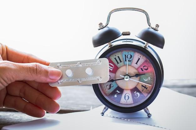 Segurando a medicina de controle de natalidade de emergência com relógio alam vintage.