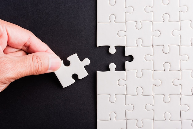 Segurando a última peça do jogo de quebra-cabeça de papel branco últimas peças colocadas para resolver o problema missão completa