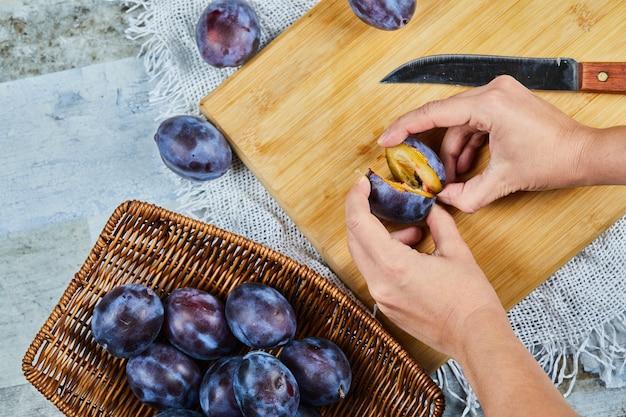 Segurando ameixa fresca em uma placa de madeira com uma cesta de ameixas