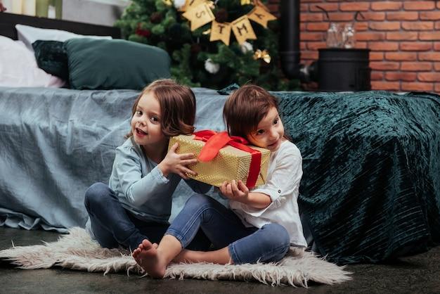 Segurando aquela caixa amarela e interessado no que está dentro. férias de natal com presentes para essas duas crianças que estão sentadas dentro de casa no belo quarto perto da cama.