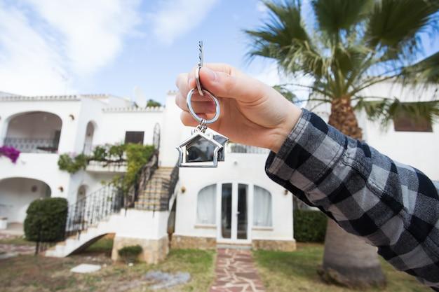 Segurando as chaves de uma casa em um chaveiro em forma de casa na frente de uma nova casa.