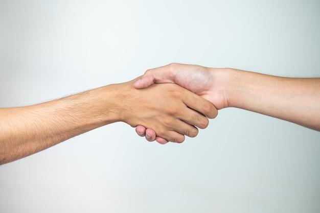 Segurando as mãos de dois homens em uma superfície branca