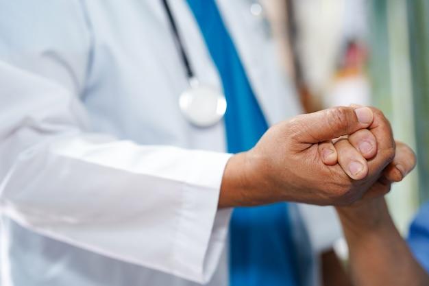 Segurando as mãos tocando paciente mulher asiática sênior com amor.