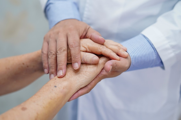 Segurando as mãos tocantes asiática sênior mulher paciente com amor.