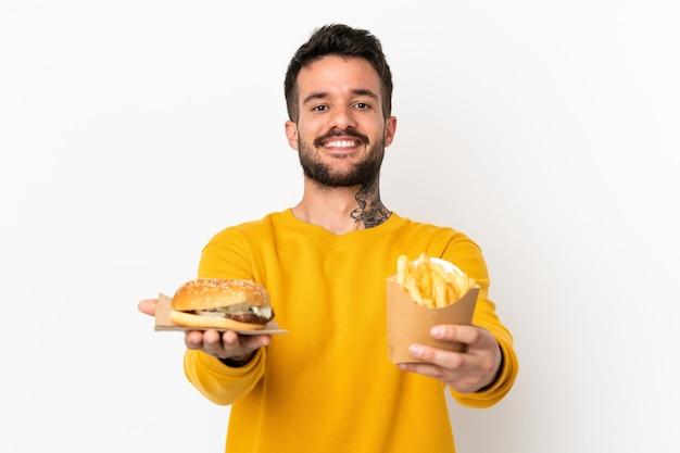 Segurando batatas fritas e cheeseburguer sobre fundo isolado
