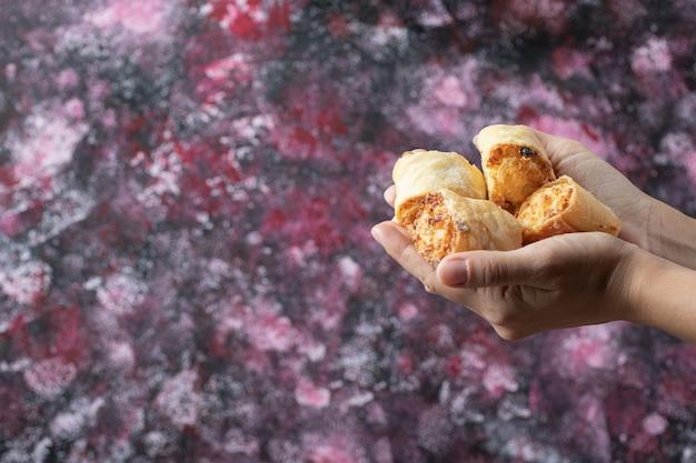 Segurando biscoitos de manteiga crocantes na mão.