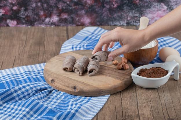 Segurando biscoitos de mini croissant na mão.