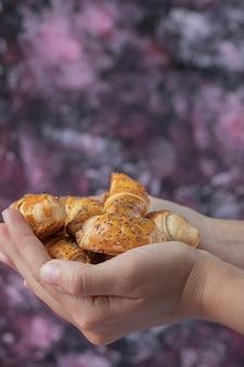 Segurando biscoitos mutaki fritos na mão.