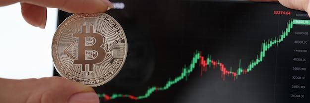 Segurando bitcoin e smartphone com gráficos de crescimento de criptomoeda