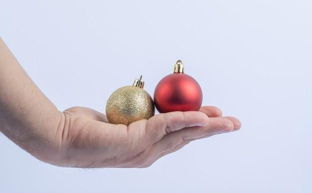 Segurando bolas brilhantes vermelhas e douradas na mão
