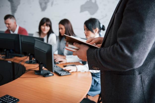 Segurando cadernos. grupo de pessoas em conferência de negócios em sala de aula moderna durante o dia