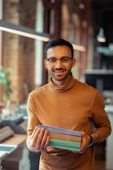 Segurando cadernos. homem bonito, trabalhando em uma fabricante de papel com cadernos coloridos