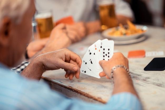 Segurando cartões. close de um homem aposentado de cabelos grisalhos usando uma pulseira segurando cartas