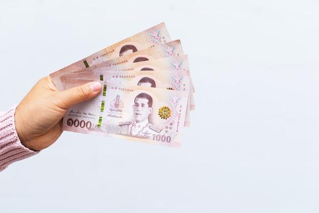 Segurando cédulas equivalem a cinco mil baht tailandeses